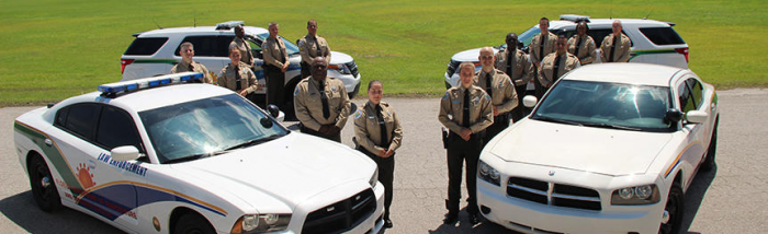FDACS officers posing at attention beside vehicles